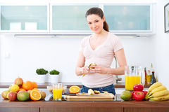 Young woman prepare fruits for breakfast. Royalty Free Stock Photography