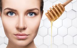 Young woman prepare for honey facial mask. Royalty Free Stock Photo