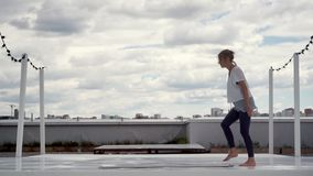 Young woman prepare to yoga practice. Girl lay out yoga mat on roof on cityscape. Young woman prepare to yoga practice in slow motion. Girl lay out yoga mat on stock footage