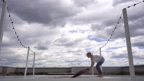 Young woman prepare to yoga practice and setting up her yoga mat in slow motion. Girl is making hand greeting namaste on roof home in background of city stock footage