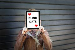 Young woman prepared for blind date with face hiding behind tablet stock images