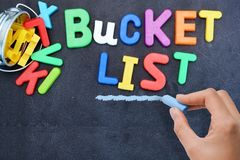 Young woman prepared for bucket list with metallic bucket and colorful plastic letters on blackboard Stock Photography