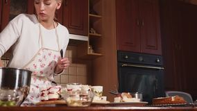 A young woman prepares desserts in the kitchen, lady finishes the sweets in cups. A young woman who prepares appetite desserts is engaged in the preparation of stock video