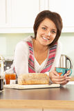 Young Woman Preparing Breakfast In Kitchen Stock Photo