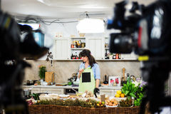 Young woman preparing for a cooking show. Young brunette woman preparing for a cooking show, surrounded by video cameras Stock Photos