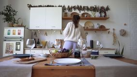 A young woman is preparing for dinner, standing in the kitchen. Loft apartments in Scandinavian style, using. Environmental materials in the interior 4k stock footage