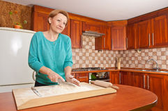 Young woman preparing dough in kitchen Royalty Free Stock Image
