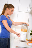 Young woman preparing drink with  blender Royalty Free Stock Photos