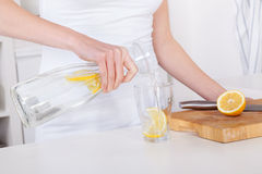 Young woman preparing and drinking lemonade in her kitchen Stock Image