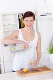 Young woman preparing and drinking lemonade in her kitchen Stock Photos