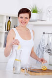 Young woman preparing and drinking lemonade in her kitchen Royalty Free Stock Images