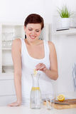 Young woman preparing and drinking lemonade in her kitchen Royalty Free Stock Photography