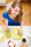 Young woman preparing a european breakfast Royalty Free Stock Image