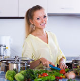 Young woman preparing food and smiling. Happy young woman preparing food and smiling at home Royalty Free Stock Photos