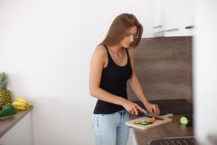 Young woman preparing a healthy meal of fresh vegetables and fruits. Royalty Free Stock Images