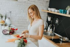 Young woman preparing healthy meal in the modern kitchen Stock Images