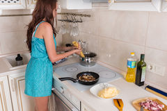 Young woman preparing a meal of spaghetti Stock Photo