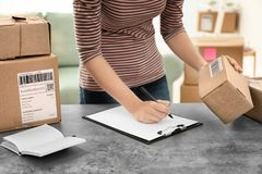 Young woman preparing parcels for shipment. To customers at table in home office. Startup business royalty free stock photo