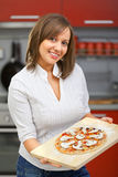Young woman preparing pizza Stock Images