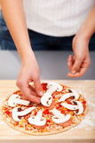 Young woman preparing pizza Stock Photography