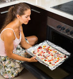 Young woman preparing  pizza  with salami Stock Photography
