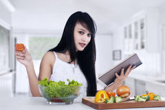Young woman preparing salad. Young woman reading recipe cooking book preparing salad in the kitchen Royalty Free Stock Images