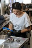 Young woman preparing the tattoo machine and inks. royalty free stock photography