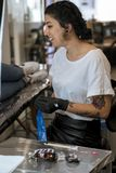 Young woman preparing the tattoo machine and inks. royalty free stock images
