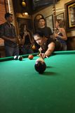 Young woman preparing to hit pool ball. Young caucasian woman preparing to hit pool ball while playing billiards royalty free stock photo