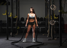 Young woman preparing to work out with battle ropes. At a gym Royalty Free Stock Photography