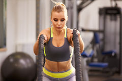 Young woman preparing to work out with battle ropes at a gym Stock Images