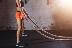 Young woman preparing to working out with battle ropes in cross fit gym. Close up crop photo of Young woman preparing to working out with battle ropes in cross Royalty Free Stock Photo