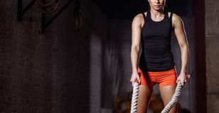 Young woman preparing to working out with battle ropes in cross fit gym. Close up crop photo of Young woman preparing to working out with battle ropes in cross Royalty Free Stock Image