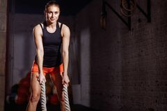 Woman preparing to working out with battle ropes in cross fit gym. Young woman preparing to working out with battle ropes in cross fit gym Stock Images