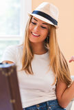 Young woman preparing for a trip. With her suitcase and clothes Royalty Free Stock Photos