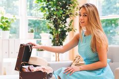 Young woman preparing for a trip. With her suitcase and clothes Royalty Free Stock Image