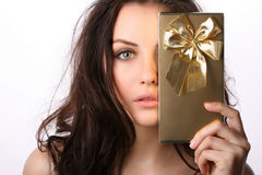 Young woman with present. Beautiful woman covers her face with present Royalty Free Stock Photography