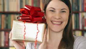 Young woman with present. Female holding golden gift box with red ribbon celebrating birthday stock footage