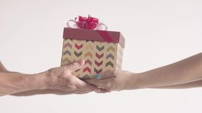 Young Woman present gift box in older woman`s hands. Happy Retired grandmother getting christmas by old hands. Celebration day stock video footage