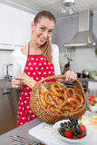 Young woman presenting a basket with fresh bavarian pretzels. Royalty Free Stock Photos