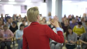 Young woman presenting a business seminar. Woman Speaker at Business Conference and Presentation. Audience at the stock footage