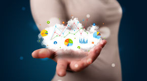 Young woman presenting cloud with charts and graph icons and sym Stock Photo