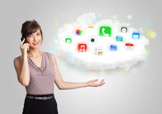 Young woman presenting cloud with colorful app icons and symbols Royalty Free Stock Photos