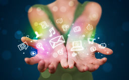 Young woman presenting colorful social media icons. Young beautiful woman presenting colorful glowing social media icons Royalty Free Stock Images