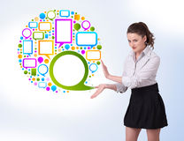 Young woman presenting colourful speach b. Young business woman presenting colourful speach bubble on bright background Royalty Free Stock Images