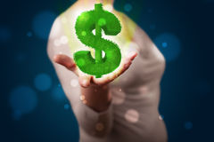 Young woman presenting green glowing dollar sign Royalty Free Stock Images