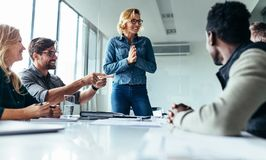 Young woman presenting her idea to colleagues stock image