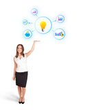 Young woman presenting light bulb with colorful graphs and diagr. Ams isolated on white Stock Images