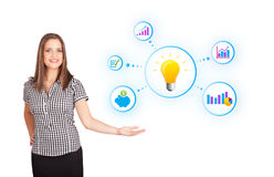 Young woman presenting light bulb with colorful graphs and diagr Royalty Free Stock Image