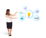 Young woman presenting light bulb with colorful graphs and diagr. Ams isolated on white Royalty Free Stock Image